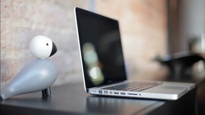 Frontal Video of a MacBook on a Desk with a Decorative Bird and a Candle Nearby a15520
