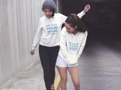 Two Girlfriends Wearing a Crewneck Sweatshirt and a Pullover Hoodie Mockup with Different Designs While Playing in the City a15712