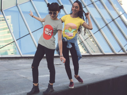 Two Girls Playing While Wearing Different Tees Mockup in the City a15754