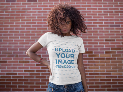 Black Girl With Wind in her Hair Wearing a T-Shirt Mockup Against a Bricks Wall a15814