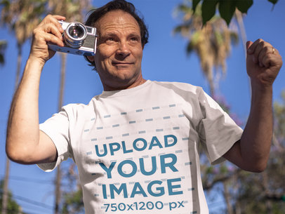 White Middle Aged Man Wearing a Round Neck T-Shirt Mockup While Taking Pictures Outdoors a15929
