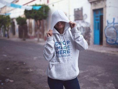 Pullover Hoodie Mockup Featuring a Girl Hiding Her Face in the Street 12721
