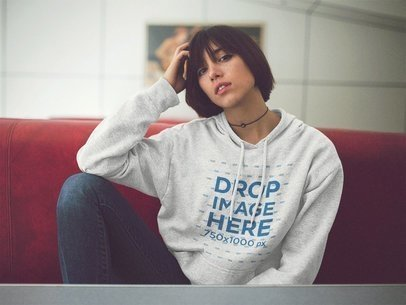 Young Asian Girl Wearing a Pullover Hoodie Mockup at a Diner Booth a12663