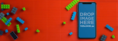 Mockup of an iPhone X Lying on a Desk with Legos a17490