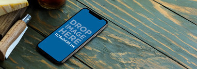 iPhone X Mockup on a Green Wooden Table a17612